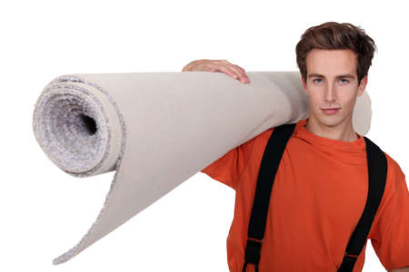 fitting room: Man carrying a roll of carpet