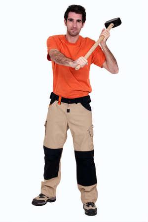 sledge hammer: A man with a sledgehammer.