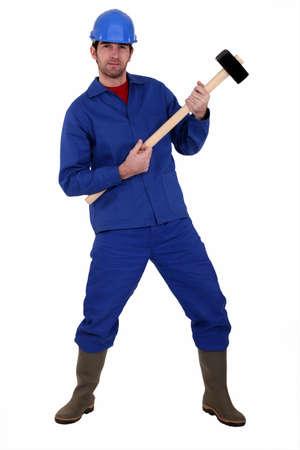 air guitar: Man playing a sledgehammer like a guitar