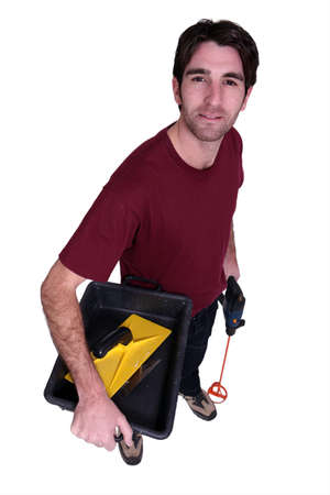 paintbucket: Man carrying pain mixing equipment Stock Photo