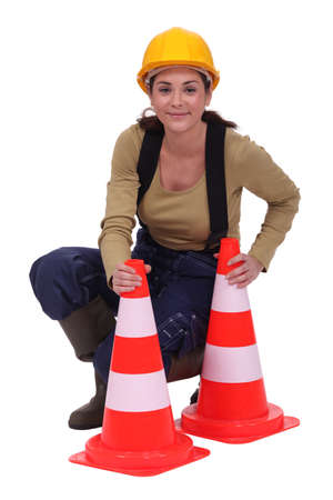 road worker: Woman kneeling by traffic cones
