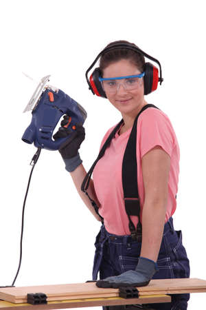 Woman using an electric saw photo