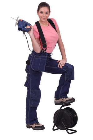 workwoman: Tradeswoman holding up a jigsaw Stock Photo