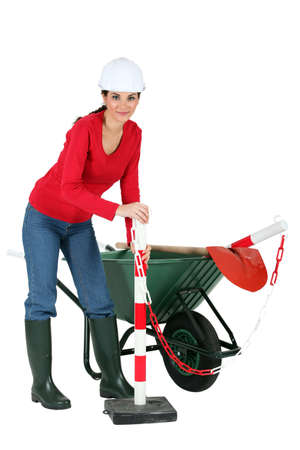 workwoman: Labourer holding a traffic marker Stock Photo