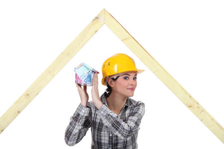 lucrative: mischievous female joiner holding miniature house