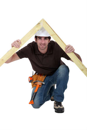 Smiling carpenter holding timber frame photo