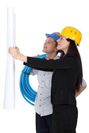 Architect and plumber looking at plans Stock Photo - 16112944