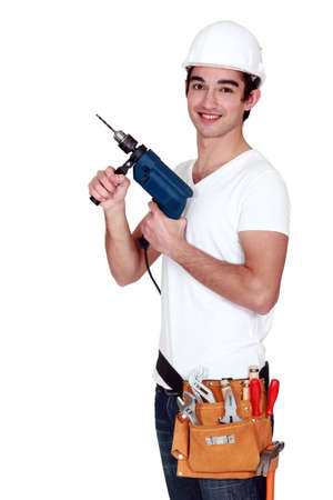 Young tradesman holding an electric screwdriver photo