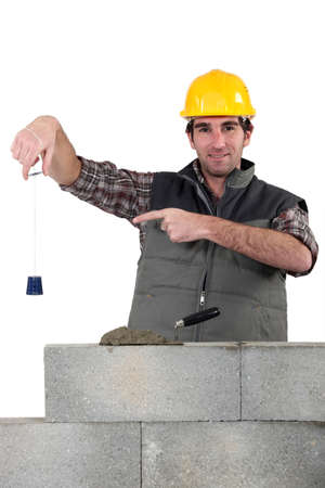 wall angle corner: Bricklayer checking that wall is level