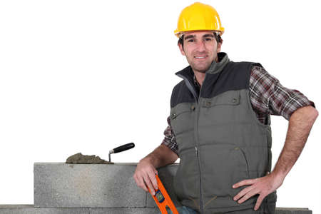 bricklayer posing near wall with arm akimbo photo
