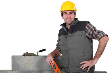 Maurer posiert in der Nähe Wand mit Arm in die Seite gestemmt