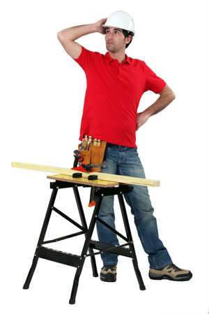 arms akimbo: carpenter with workbench looking puzzled Stock Photo
