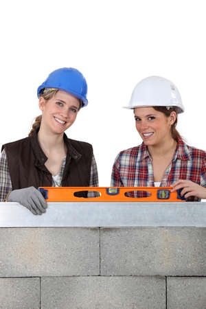 Two woman stood by wall holding spirit level photo