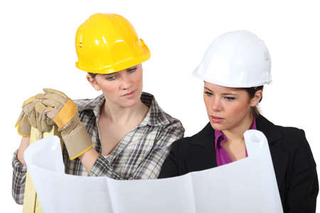 deciding: Construction worker looking at a plan with an engineer Stock Photo