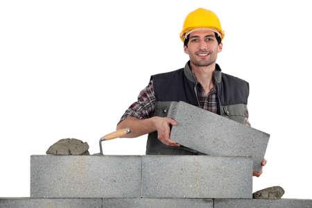 formwork: Mason carrying bricks Stock Photo