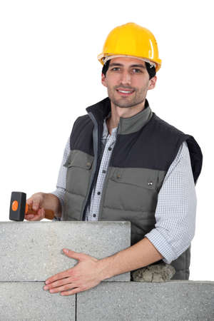 laborers: Builder hammering wall