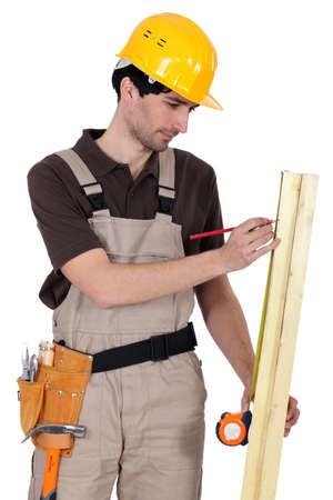 Tradesman measuring a plank of wood photo