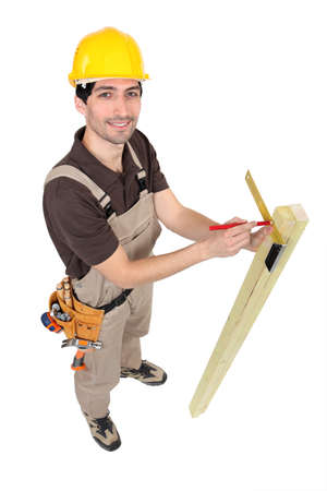 Tradesman using a try square to measure an angle photo