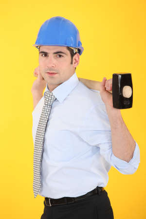 architect holding hammer against yellow background photo