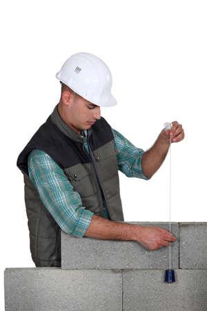 plumb: Mason checking a wall with a plumb bob