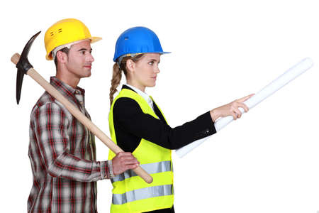 unskilled worker: Construction worker standing next to a civil engineer