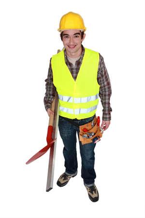 Man wearing reflective jacket and holding spade photo
