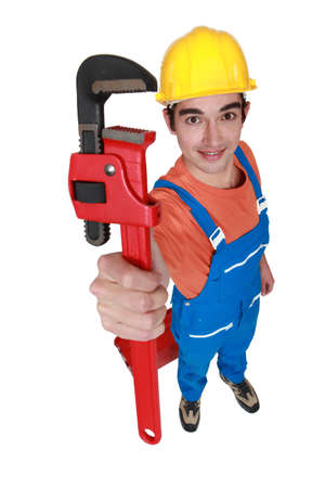 hard worker: Tradesman holding up a pipe wrench Stock Photo