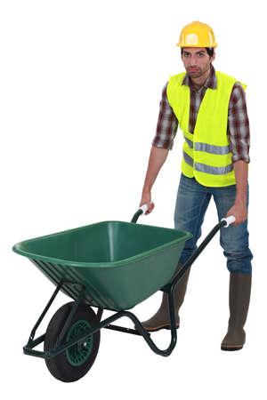 obrero: Trabajador Unfriendly empujando una carretilla