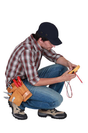 kneeled: A kneeled electrician with a voltmeter  Stock Photo