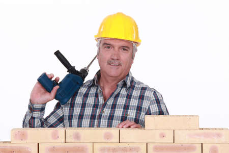 Tradesman holding a power tool and standing behind a brick wall Stock Photo - 16119673
