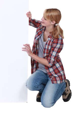 mujer arrodillada: Mujer que coloca la placa blanca Foto de archivo