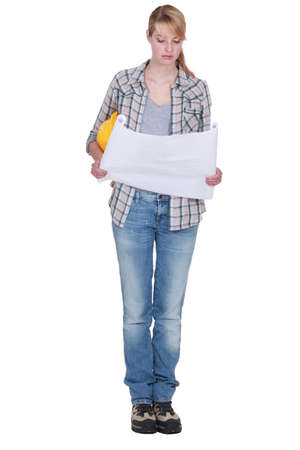 tradeswoman: Tradeswoman looking at a blueprint