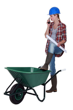 ordinate: Female construction worker stood with wheelbarrow