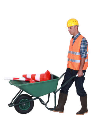 bricklayer with wheelbarrow and construction cone photo