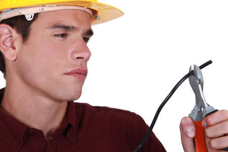 Man carefully cutting electrical wire Stock Photo - 16119592