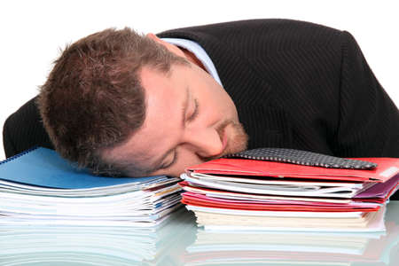 burdened: Businessman asleep on a pile of paperwork