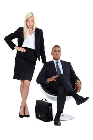 finance director: Businessman sitting in a chair next to his glamourous assistant Stock Photo