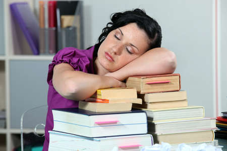 fatigued: Overworked woman sleeping on a stack of books
