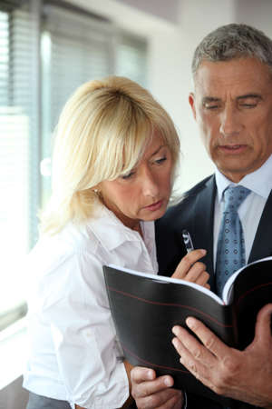 mature businessman consulting his agenda with blonde secretary by his side Stock Photo - 16190365