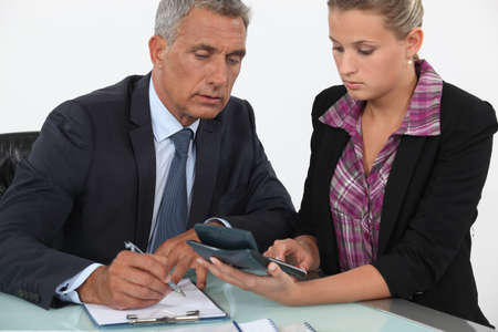insolvency: Businessman and woman using a calculator