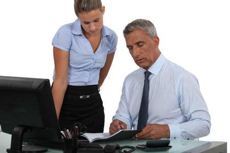 revisando documentos: Jefe y empleado trabajando juntos Foto de archivo