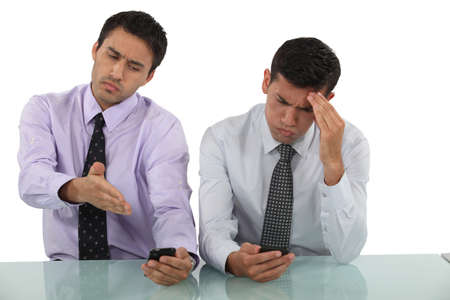 Businessmen receiving bad news via text message photo