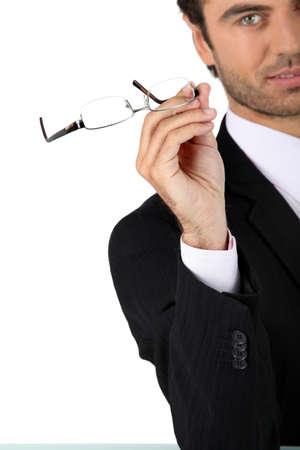 tomando: Homem tirando os óculos