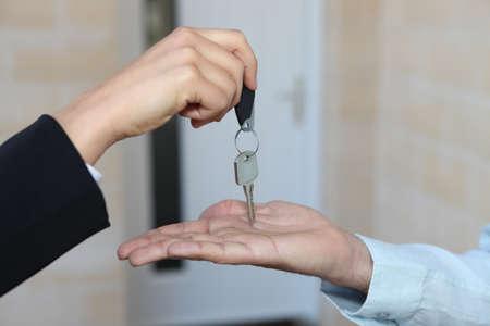 hand key: Estate-agent handing over house keys