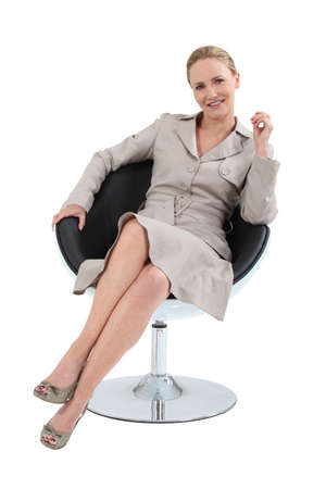 designer chair: Woman in a suit sitting in a designer swivel chair