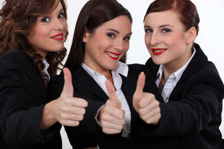 Three businesswomen giving the thumbs-up photo