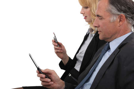 55 to 60: Business partner both checking e-mails on cellphone Stock Photo