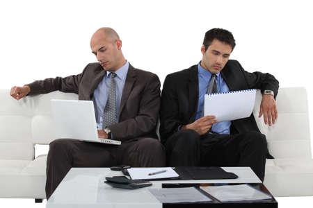 Two businessman sat on sofa checking through document photo