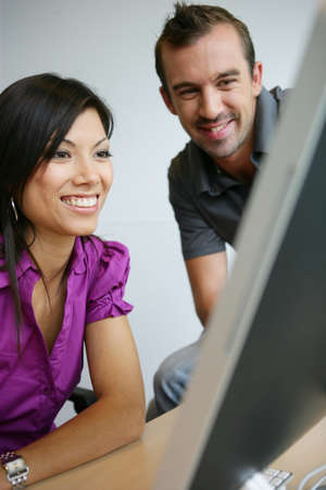 happy young woman and man working on laptop photo