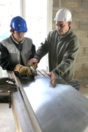 modern manufacturing: Apprentice being shown how to cut sheet metal